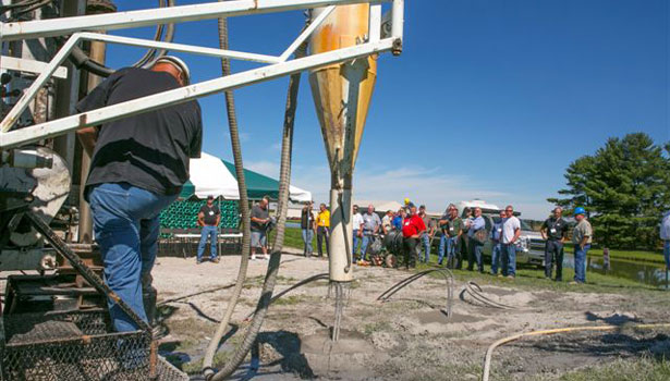 One of several groups watch as a borehole is filled with thermal grout.
