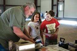 Marty Peifer shows a pair of children an air quality reading