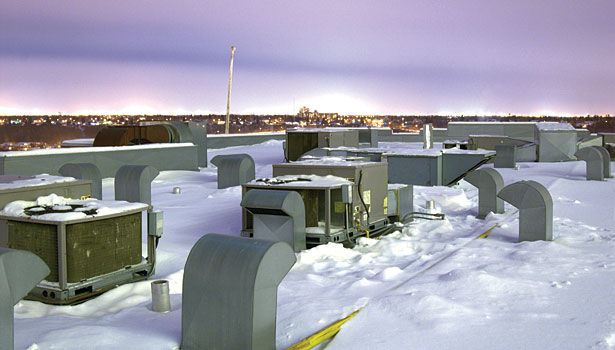 snow dons a rooftop as the sun peaks over the horizon
