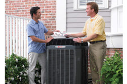 contractor and homeowner standing next to a/c unit