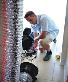 A BPI-certified professional performs a duct leakage test.