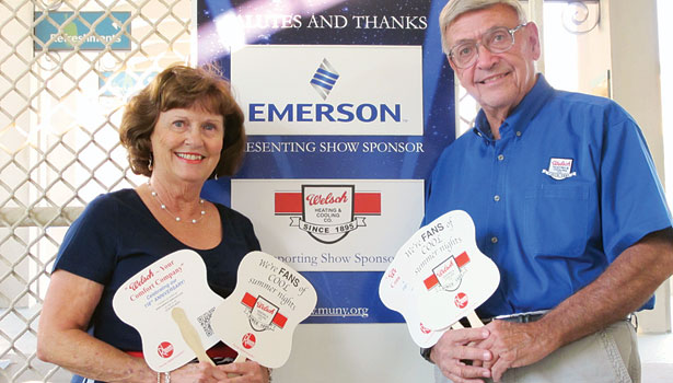 Butch Welsch, right, and his wife Carol, pose with fans his company, Welsch Heating & Cooling, handed out at The Muny, a St. Louis outdoor musical theatre.
