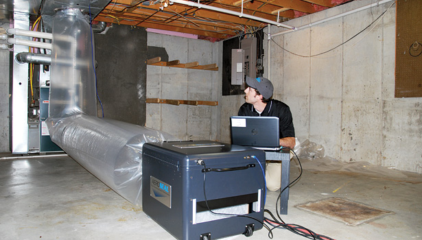 An Aeroseal contractor works on sealing the ductwork inside a home. The aerosolized vapor travels throughout the ductwork, automatically sealing leaks from the inside. (Photo courtesy of Aeroseal)