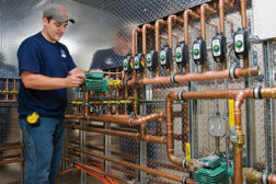 A technician with Woburn, Mass.-based Central Cooling and Heating installs a variable-speed Delta-T Taco circulator and eight Zone Sentry zone valves for a new home's radiant heat system.