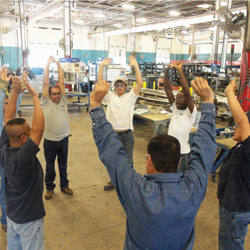 TDIndustries' prefabrication shop crew participates in stretching exercises before they begin their shift.