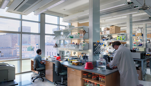 Laboratory technicians work in the Molecular Medicine Research Building at Virginia Commonwealth University in Richmond, Va., directly below the energy-efficient chilled beam system installed above the lab benches.