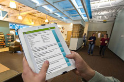 NREL Engineer Nicholas Long uses simuwatt Energy Auditor on his iPad to audit the lighting in a café on NREL's campus