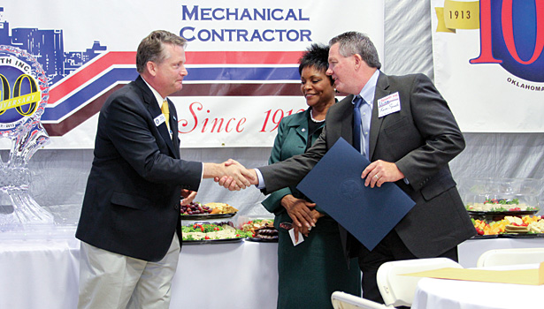 Labor commissioner Mark Costello, left, congratulates Kevin Spaeth, right, as Oklahoma State Sen. Constance Johnson, middle, looks on at the company's celebration.