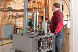 Dustan Keuenhoff, service technician with Rymes Propane & Oil, Concord, N.H., completes a residential installation of a gas-fired, modulating-condensing boiler.