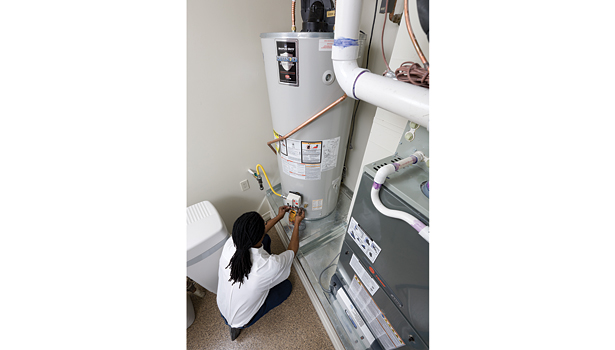 Ricky Robertson, service manager, Gilbert Plumbing, Mesa, Ariz., services a water heater. Manufacturers are making rapid increases in efficiency for both water heaters and boilers.