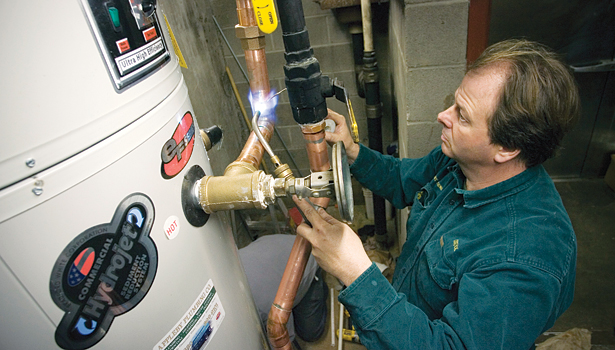 Chuck Appleby, owner, Appleby Plumbing Co., Old Saybrook, Conn., solders the hot water supply line to a restaurantâ??s kitchen.