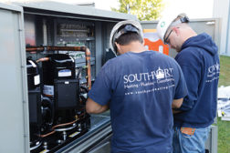 Southport Heating, Plumbing, and Geothermal technicians Josh Pothast (left) and Nicholas Draeger (right) install a 30-ton Modine Atherion rooftop packaged unit.