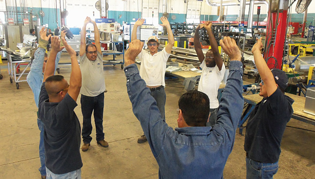 Workers at TDIndustries stretch before the workday as part of a large wellness program put in place by the company.