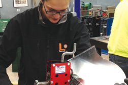 Heidi Brown uses a rotary hand flange forming machine to put a ¼-inch bend in the metal so it can be placed inside of a Pittsburgh lock to form the duct together.