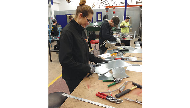 Apprentice Heidi Brown uses sheet metal seamers to put a �½-inch bend on the metal.