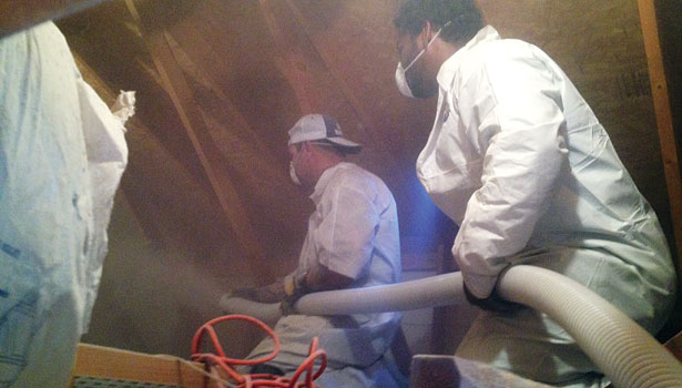 Insulation installers Nathan Soudani (left) and Dajaunta Chatman (right)work in an attic to blow in cellulose insulation.