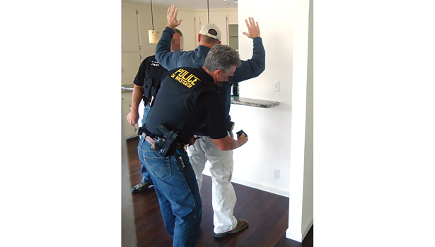 Police arrest an unlicensed contractor during a California licensing sting. (Photo courtesy of California Contractors State License Board)