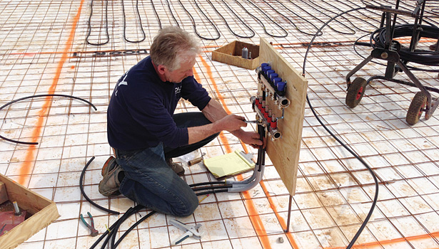 Lead technician Harvey Youker of Foley Mechanical connects �½-inch PEX tubing to a manifold on a new home in Warrenton, Virginia.