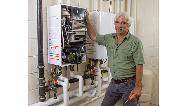 Bob Avila of Avila Plumbing and Heating, Lawrence, Massachusetts, replaced two 400,000-Btu boilers and a 300-gallon storage tank with three Navien NPE-240A tankless water heaters at the Brooks School. (Photo courtesy of Navien)