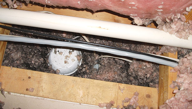 This discolored fiberglass insulation around a can light in an attic is a clue that air movement has been taking place. The insulation acts as a filter as air moves through it.