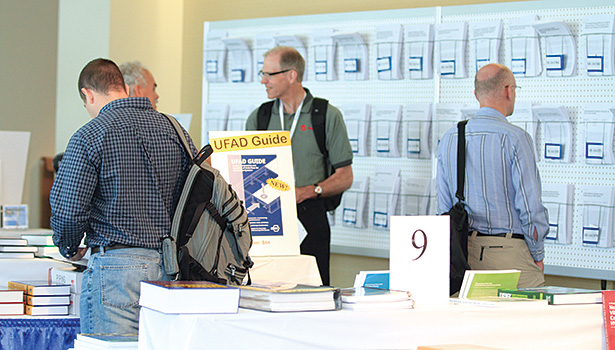 A couple of conference-goers check out the offering of books provided at the annual conference.