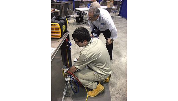 Procedures for proper refrigerant recovery and recycling are undertaken by a 2014 SkillsUSA National Championship contestant under the watchful eye of judge Warren Lupson.