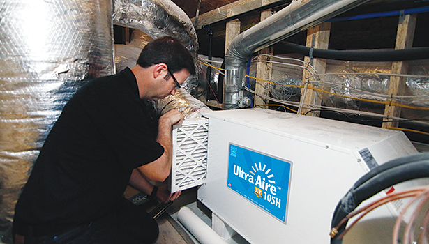 Matt Risinger, owner of Risinger Homes in Austin, Texas, works on a Ultra-Aire XT105 dehumidifier. As buildings get tighter, the need for dehumidification is going to rise, said Nikki Krueger of Ultra-Aire.
