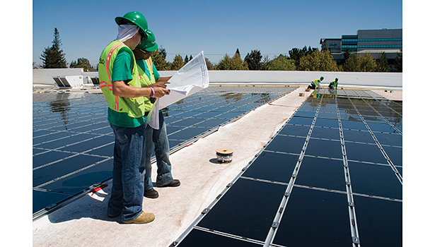 Workers look at plans on top of a big-box store with solar panels.