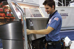A service technician is recharges a small refrigeration unit with HFC-134a. Under an EPA proposal, the use of that refrigerant would not be allowed in similar equipment manufactured in 2016 and beyond.