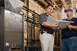 Dan Foley (left), president of Foley Mechanical Inc., reviews the mechanical design on a new geothermal project in Virginia with lead tech Brian Golden.