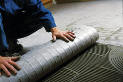A professional tile setter installs a Nuheat Mat onto the subfloor. A certified electrician will be brought in to connect the wiring system.