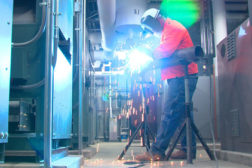 A pipefitter performs electric arc welding to attach a fitting.