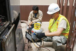 HVAC specialists A1C Samuel Groover and Roy Matsuoka digitally monitor refrigeration weight and pressure of a chiller in order to correctly recharge the unit.