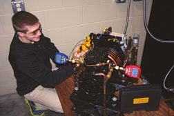 Figure 1. A student service technician sets up an ammeter and Bluetooth high- and low-side pressure gauges on a compressor after fixing a leak near the liquid line solenoid valve and charging refrigerant to a glass door reach-in freezer.