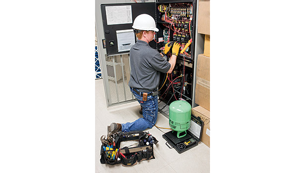Joey Donithan, journeyman service technician, Crockett Facilities, Bowie, Maryland, performs preventive maintenance on a computer room a/c (CRAC) unit.