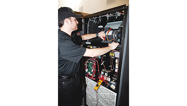 Tony Mori, senior HVAC estimator/planner at Crockett Facilities, inspects the belt tension on a computer room a/c unit (CRAC).