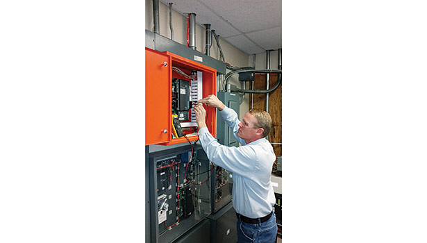 A service technician from Entech Sales & Service Inc. performs visual and physical voltage checks on various input/outputs for a direct digital field controller.