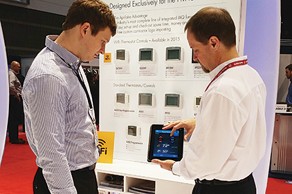 Mike Rimrodt (right), Aprilaire, shows Alex Fricke (left), Derse Inc., how to control a home�¢??s indoor environment remotely through a Wi-Fi-capable thermostat during the 2015 AHR Expo in Chicago.