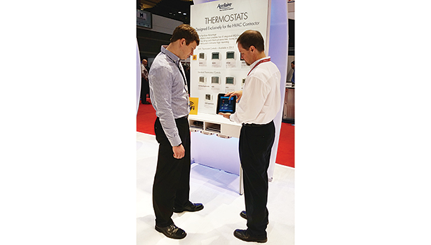 Mike Rimrodt (right), Aprilaire, shows Alex Fricke (left), Derse Inc., how to control a homeâ??s indoor environment remotely through a Wi-Fi-capable thermostat during the 2015 AHR Expo in Chicago.