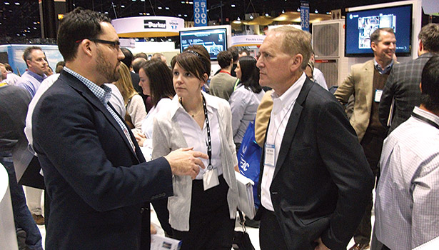 At the Trane booth, Gary Michel (right), president of Trane Residential, confers with colleagues.