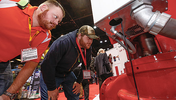 Michael Rixmann (left), service manager, and Anthony Rehling (right), service technician, Benck Mechanical Inc., Somerset, Wisconsin, take a close look at industrial equipment at the show.