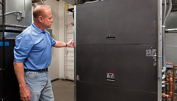 ClimateMaster representative Tony Henkel examines the Tranquility�® Compact (TC) Belt Drive Series.