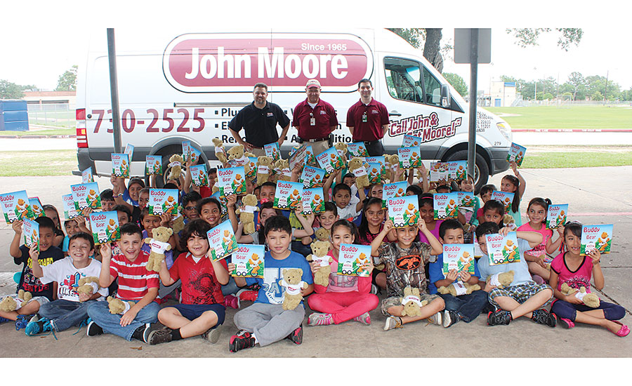 John Moore Home Services employees (left to right) Brian Menn, pest control manager; Glen Gamache, senior inspector; and Derek Lopez, accounting, pose for a picture with Bane Elementary students