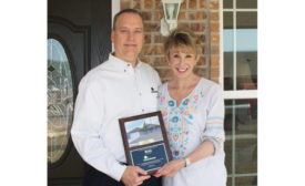 Rick Aldridge (left), president, ClimateMaster Inc., and Ann Felton (right), president of Central Oklahoma Habitat for Humanity, celebrate the 400th home built with geothermal heat pumps donated by ClimateMaster.