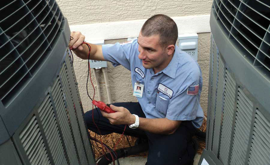 Anthony Leo, a service technician with Advanced Air in Fort Myers, Florida, performs a maintenance reading during a service call.
