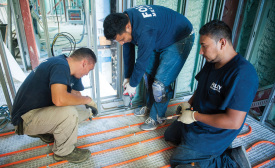 TUBING TRIO: Technicians for Foley Mechanical Inc. in Lorton, Virginia, secure Watts Radiant PEX tubing to the floor of a facility in Washington, District of Columbia.