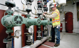 Steve Bothell, Weldin's lead foreman, attaches a pump pressure gauge to one of the main Taco LoadMatch pumps for the two 3-inch primary mains at this Professional Military Education Center.