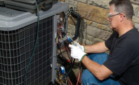 "An HVAC technician retrofits a residential air conditioning unit from R-22 to Freonâ""¢ MO99. Photo courtesy of the Chemours Co."