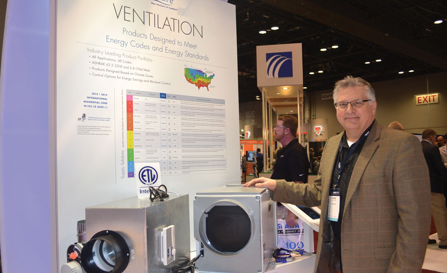 Chris Chase, product marketing manager, air cleaners, thermostats and zone comfort controls, Aprilaire, stands next to the manufacturer's new Model 8191 and 8192 whole-home ventilators with dehumidification.