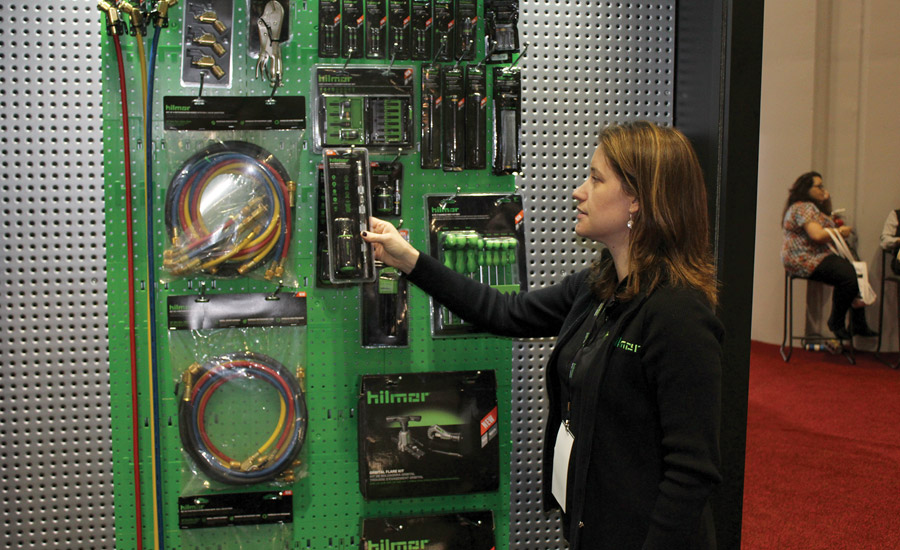 Emily Bavaro, director of marketing, Hilmor, looks over some of the company's newest tools on display at the AHR Expo.